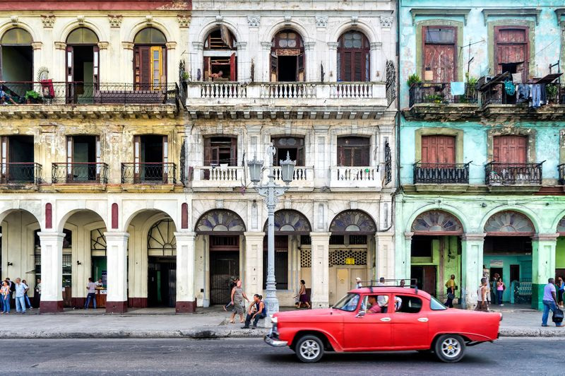 Old buildings in Havana with classic car.