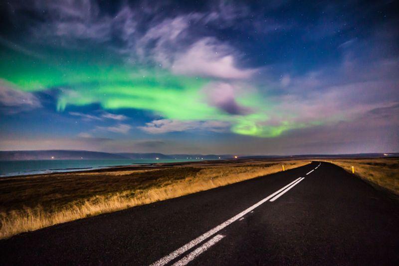 Северное сияние над дорогой в Исландии
