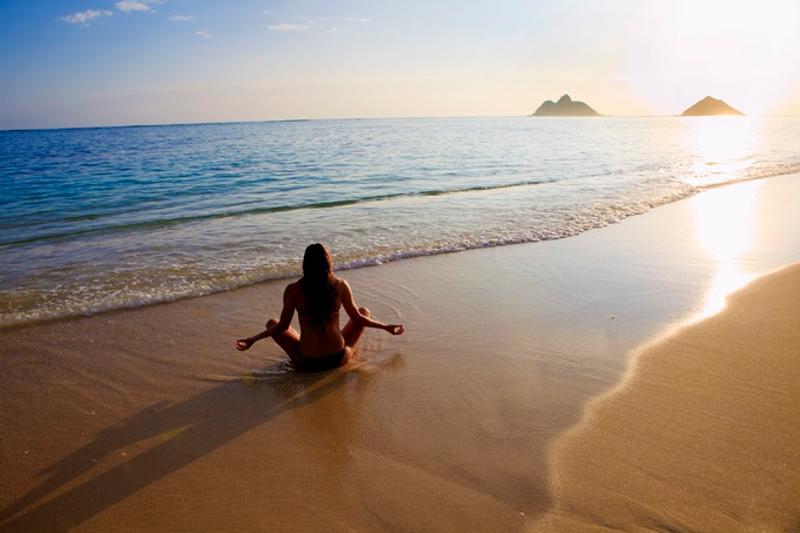 A woman holds a yoga pose on a beach.