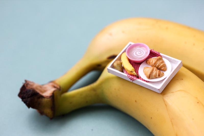 Инсталляция из игрушечного завтрака с капучино и круассанами на настоящем банане