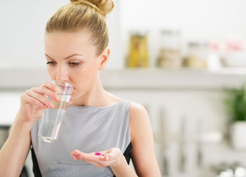 Young housewife eating pills and drinking water