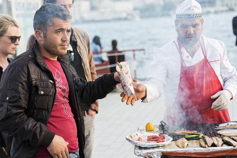 Турок покупает балык-экмек на набережной в Стамбуле