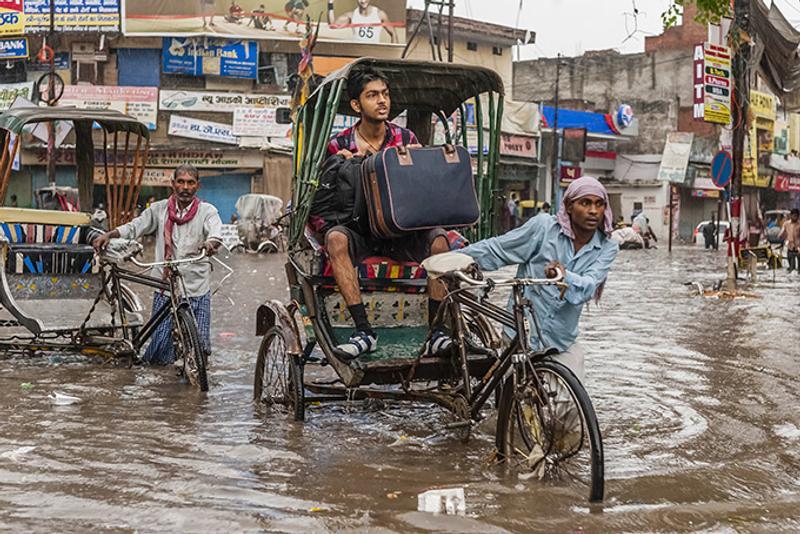 Велорикша везет пассажира во время сезона дождей в Индии