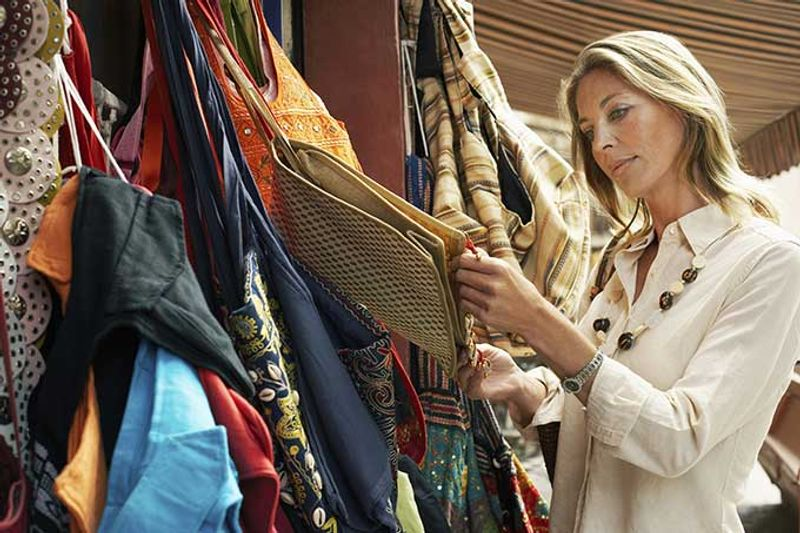 A woman shops for scarfs.
