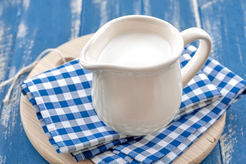 Кувшин молока на синих клетчатых полотенцах