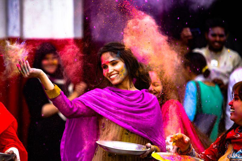 Девушка разбрасывает порошковую краску на фестивале Холи в Индии