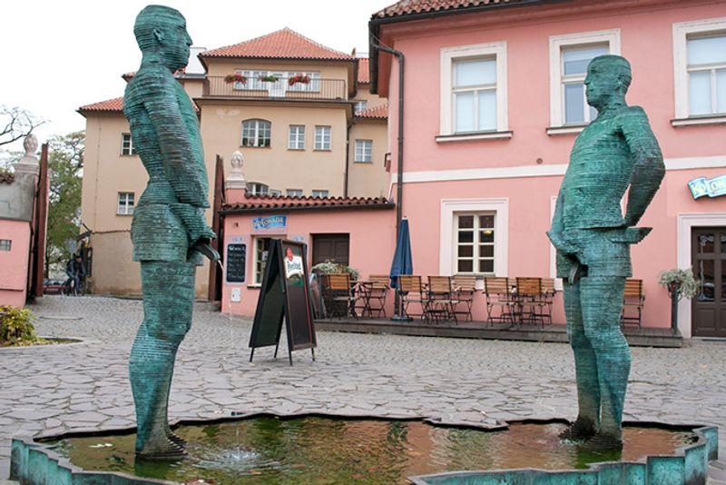 Достопримечательности Праги: статуи писающих мужчин у музея Франца Кафки.
