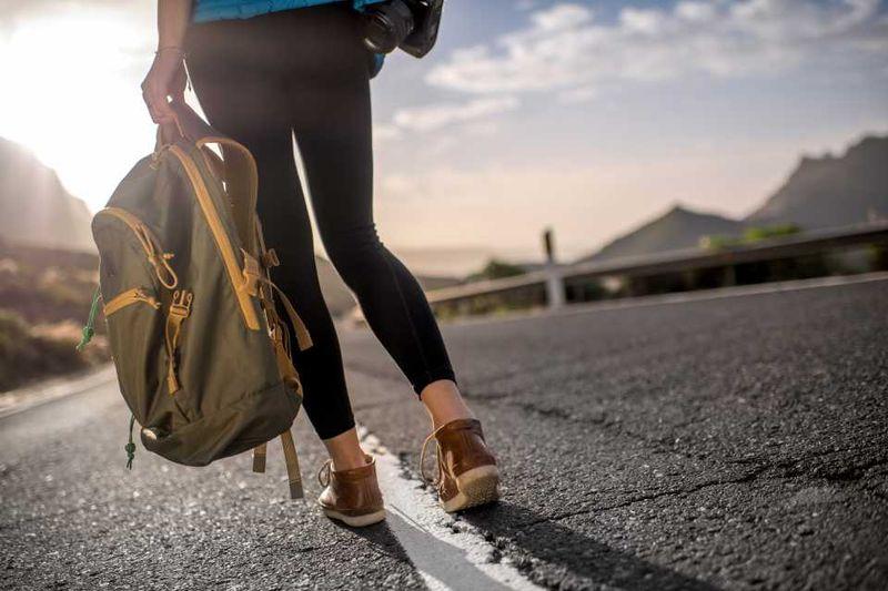 Автостоп в Грузии: девушка с рюкзаком и камерой голосует на трассе