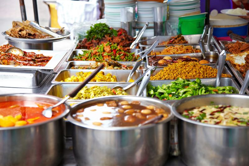 Close-up of Thai street food dishes in metal trays and pots