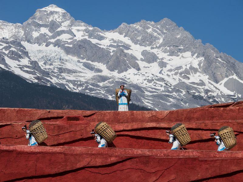 Женщины народности наси с корзинками на спинах в горах Лицзяна