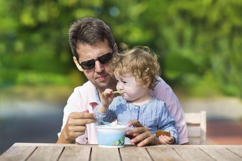 Отец с ребенком едят мороженое