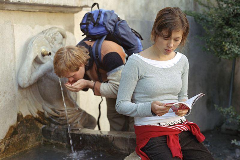 Молодые бэкпэкеры у фонтана