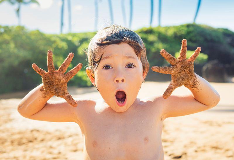Ребенок на пляже с открытым ртом и руками в песке