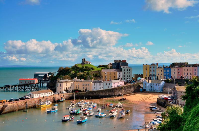 View of Tenby Harbour, multi-coloured houses on a sand beach, with Castle Hill