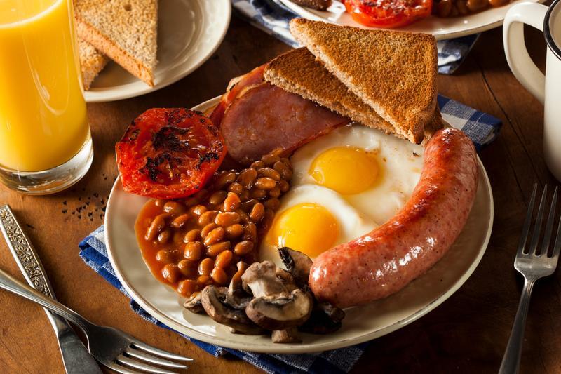 Традиционный полный английский завтрак с беконом, сосиской, помидорами, грибами, фасолью и яичницей