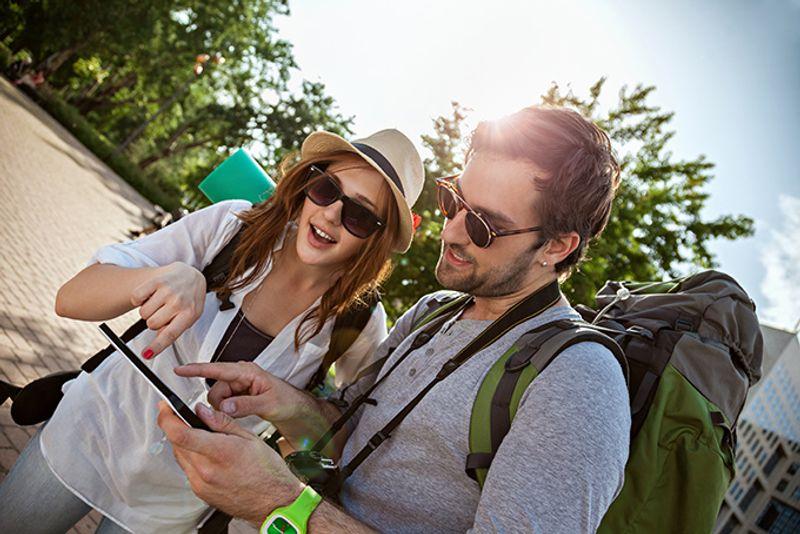 Пара туристов с рюкзаками гуляет по городу