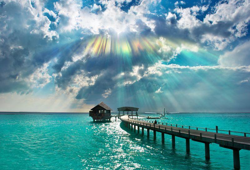 Разноцветные лучи солнца над лазурным морем, пирсом и хижиной на Мальдивах