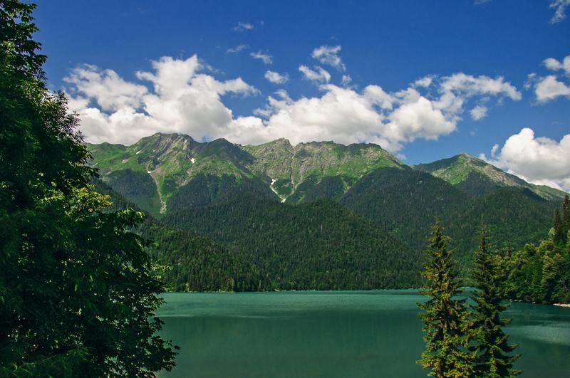 Вид на озеро Рица в окружении гор и деревьев