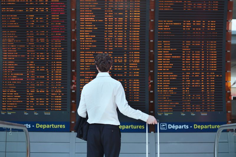 Man looking up at departures board
