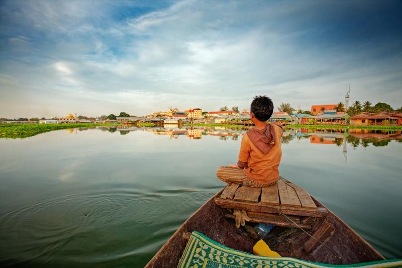 Мальчик на лодке в Камбодже