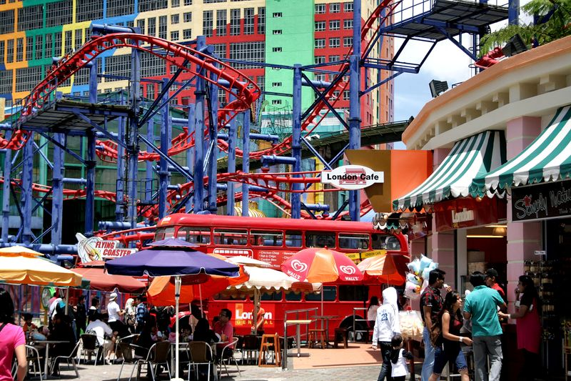 View of theme park with café, roller coaster and hotel in background