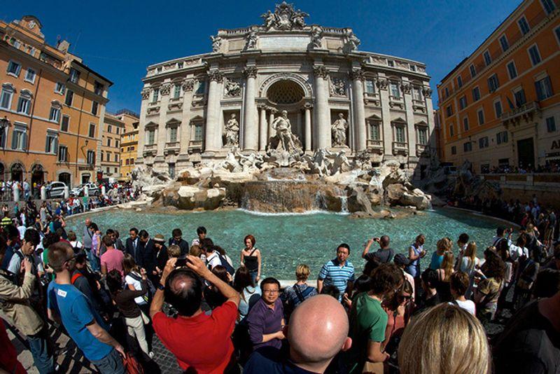 Толпы туристов возле фонтана в Риме во время летних отпусков