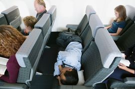 Man sleeping in three seats - turn your economy fare into a first-class experience