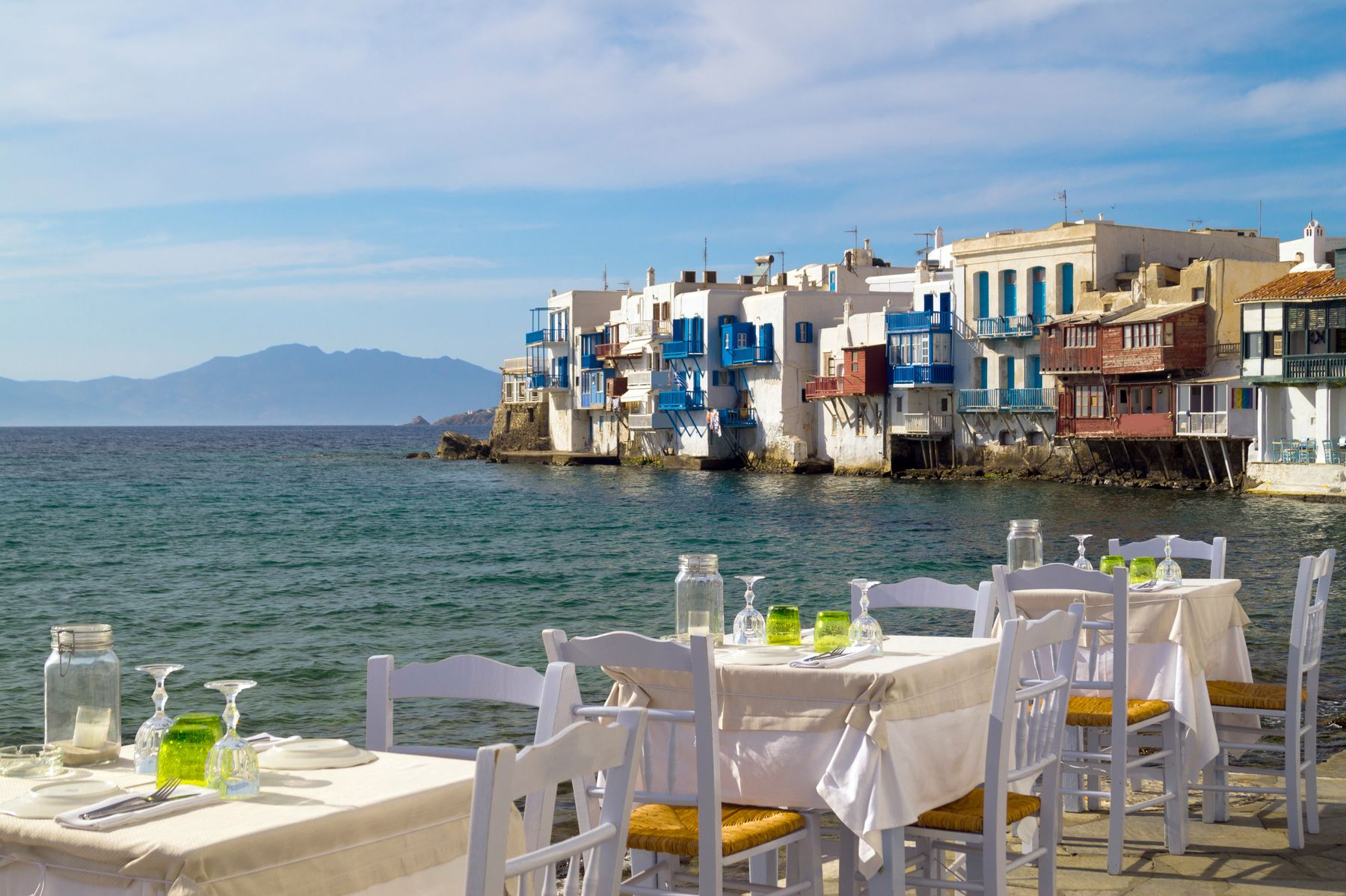 Now that Greece is open you can enjoy meals in outdoor restaurants, with tables and chairs set right beside the sea in Santorini, with views out to ramshackle buildings in the foreground and further mountain in the back.