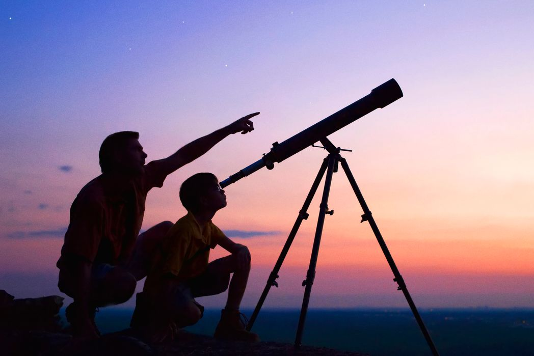 Father and son looking at the stars through a telescope