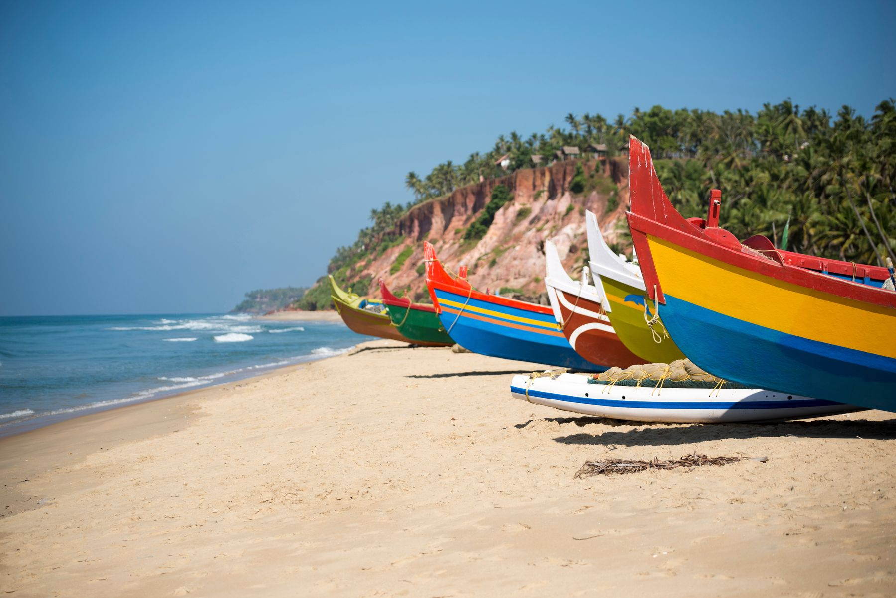 colourful wooden boats by the shore in kerala, india