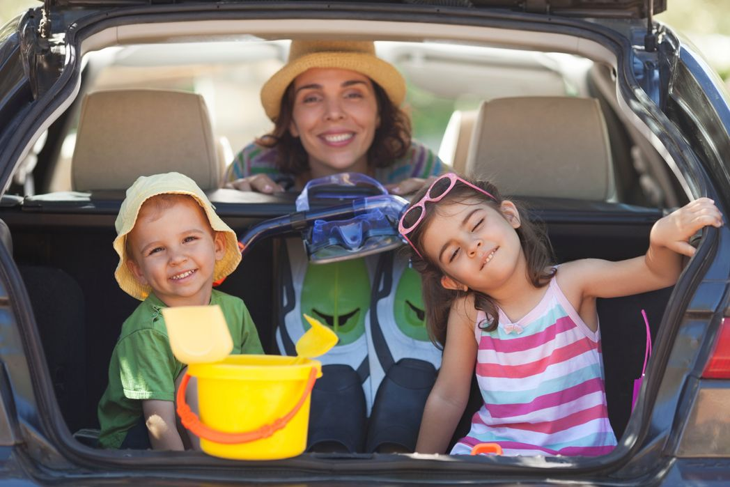 Mother and two kids at the back of a car - road trip with family