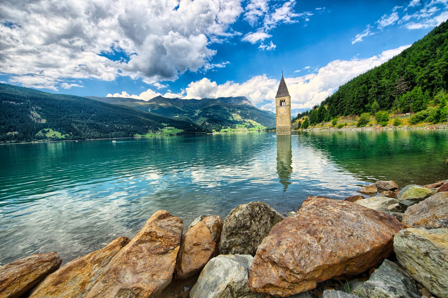 A church bell tower peeks out of the glacial lake in Alto Adige, Italy.