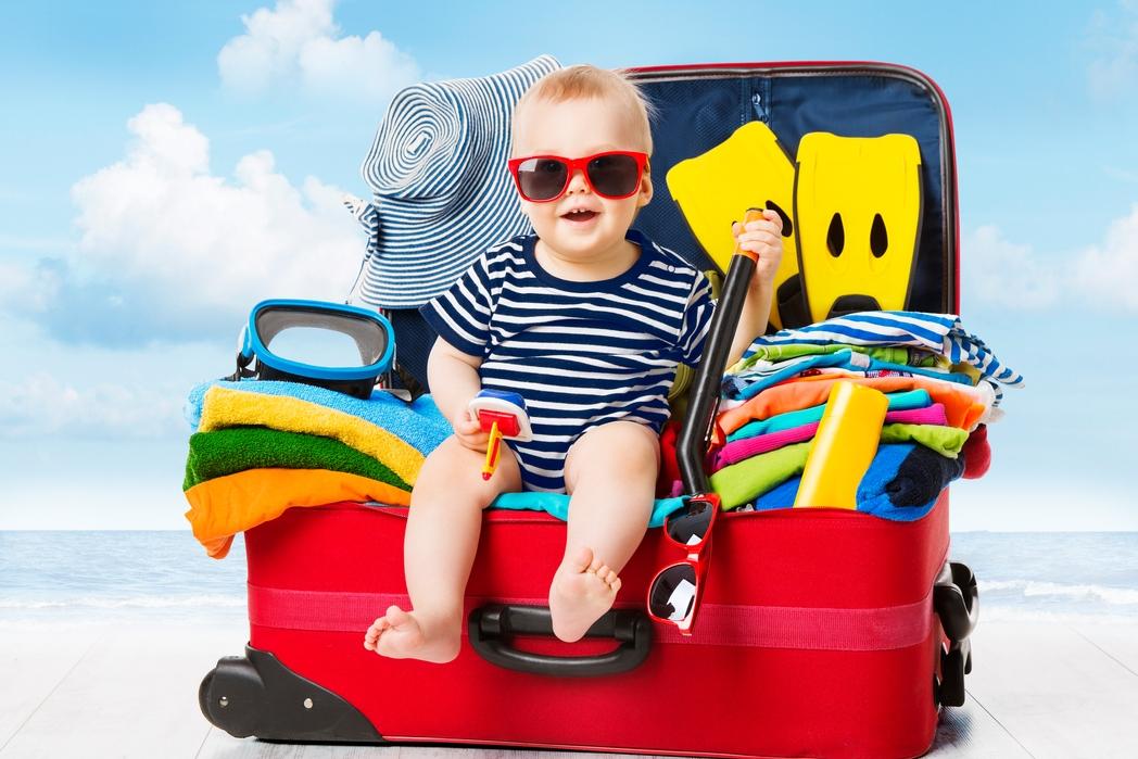 Μικρό παιδί πάνω σε βαλίτσα ετοιμάζεται για καλοκαιρινές διακοπές - tips για φθηνές διακοπές με παιδιά