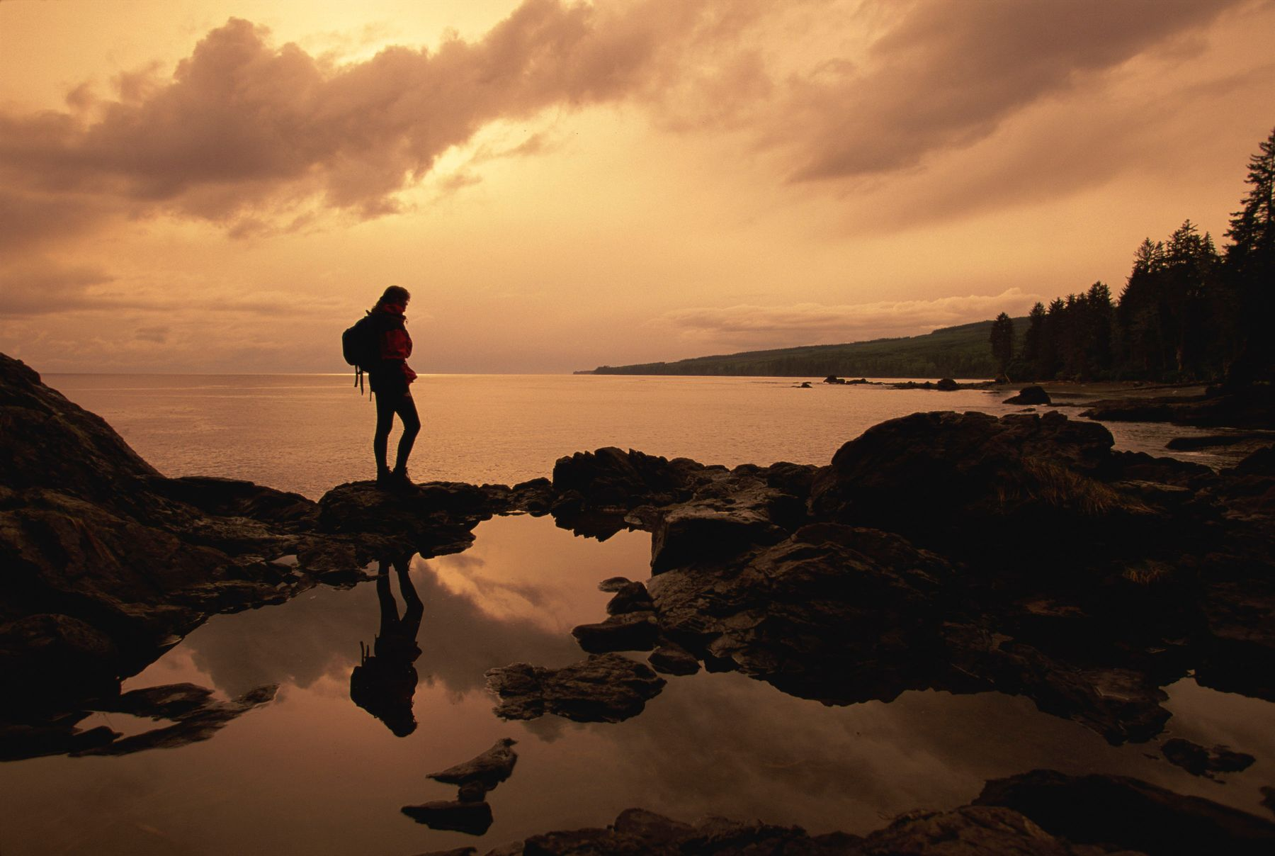 hiker standing on rocks along the shore of Vancouver Island at sunset