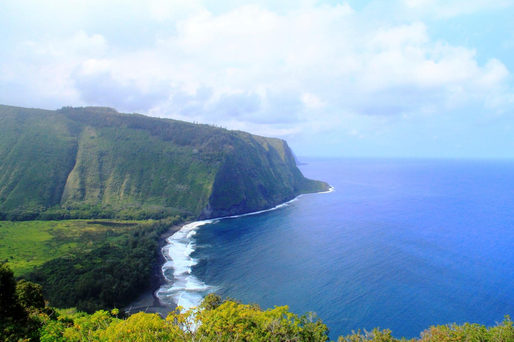 blue waves meet a green mountain from hawaiian glampsite