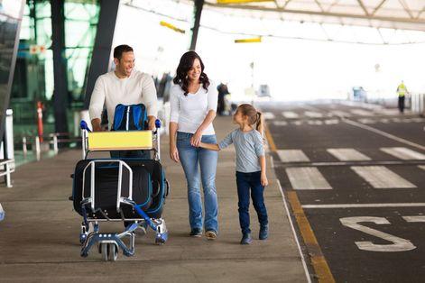 Γονείς με το παιδί τους μεταφέροντας τις αποσκευές τους στο αεροδρόμιο