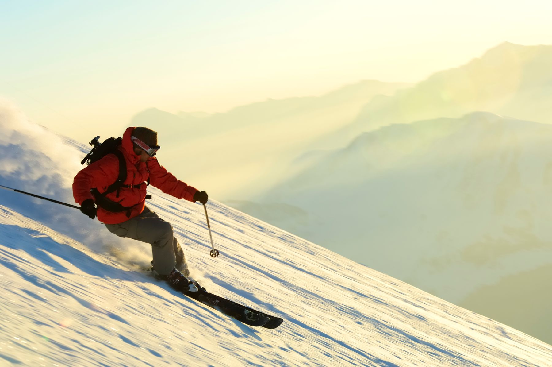 Man skiing down slope; how to ski on a budget in Australia and New Zealand