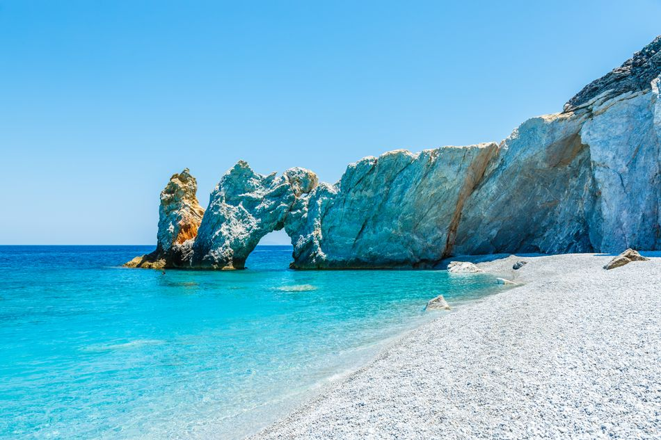 A natural arch towers over the turquoise sea of Skiathos, Greece