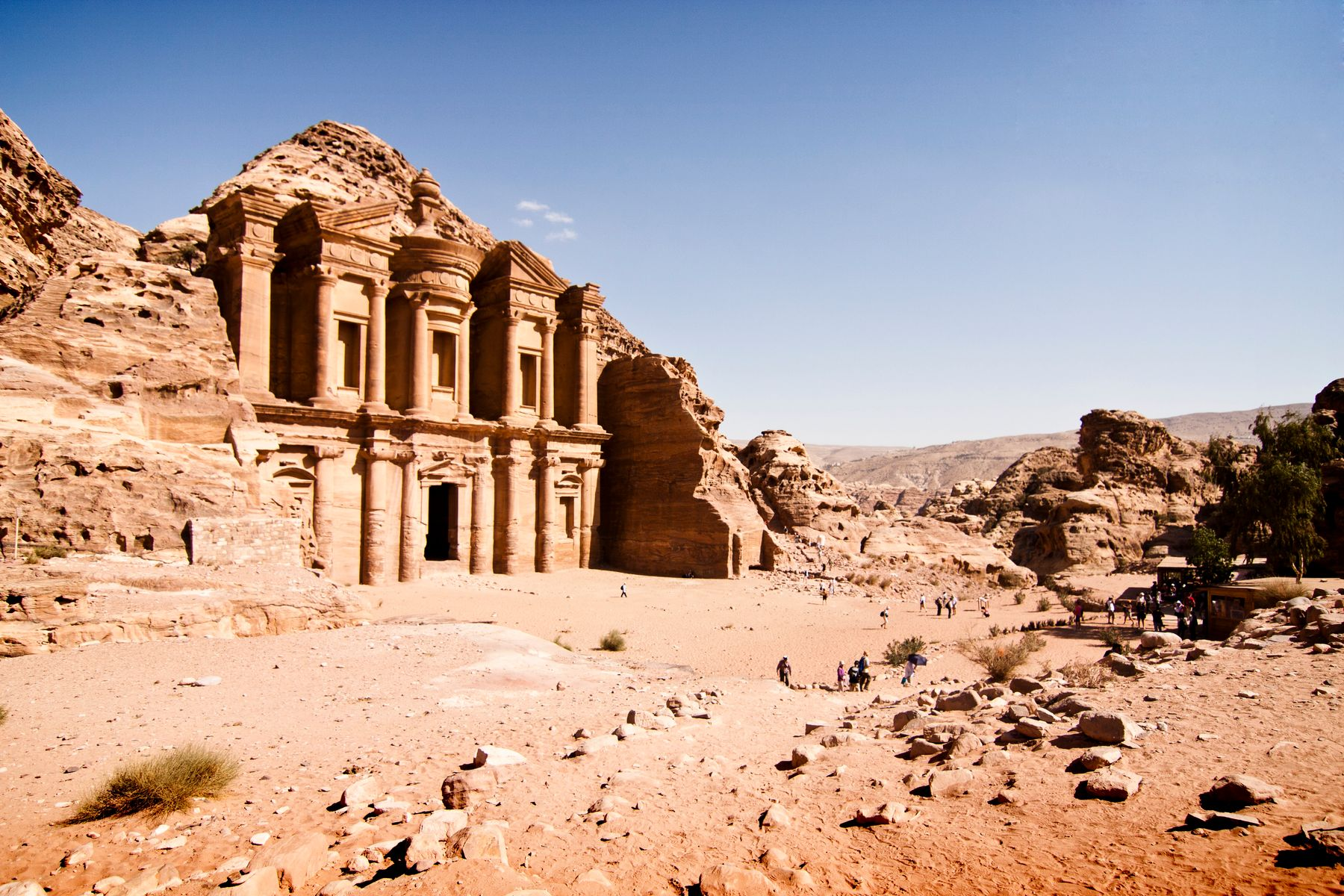 The ruins of Petra in Jordan: a beautiful building carved into the desert rock, dwarving tourists in the foreground