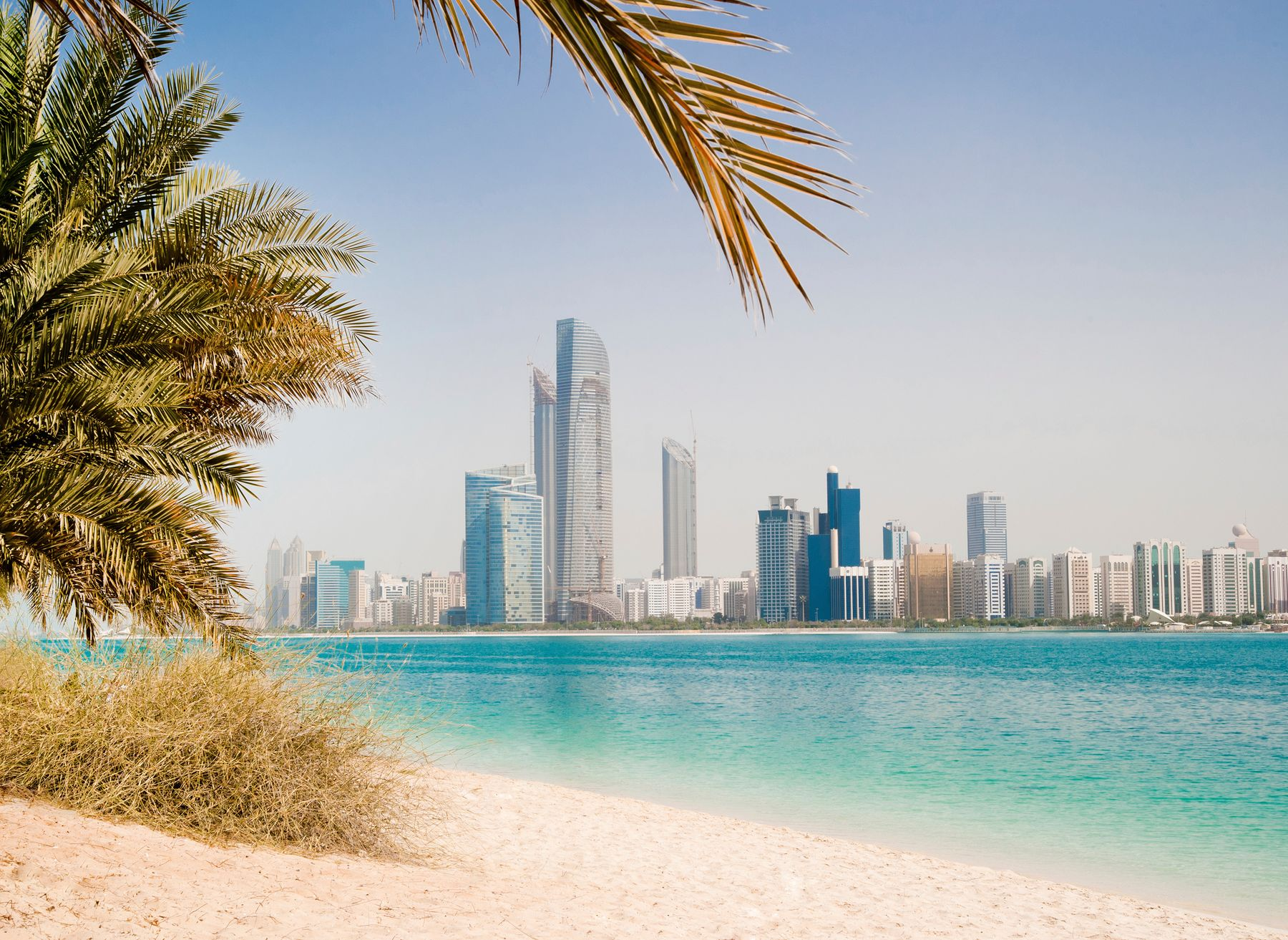 Dubai skyline as seen from a beach with palm trees in the foreground
