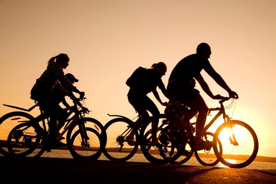 Οικογένεια σε ποδήλατα το ηλιοβασίλεμα