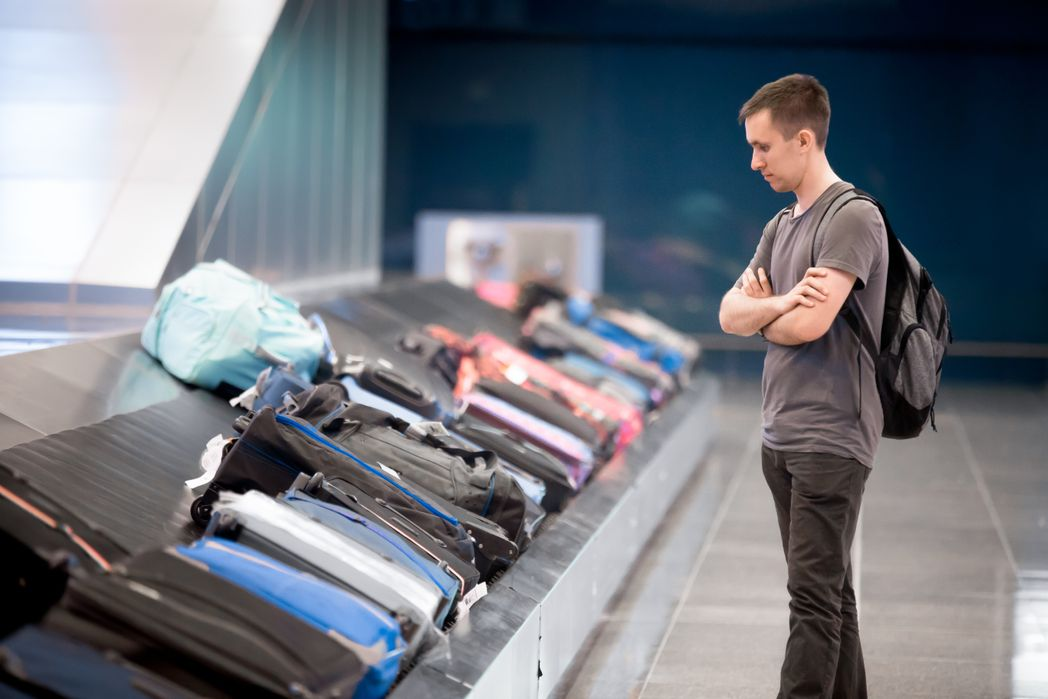 Man waiting for his suitcase in the baggage claim