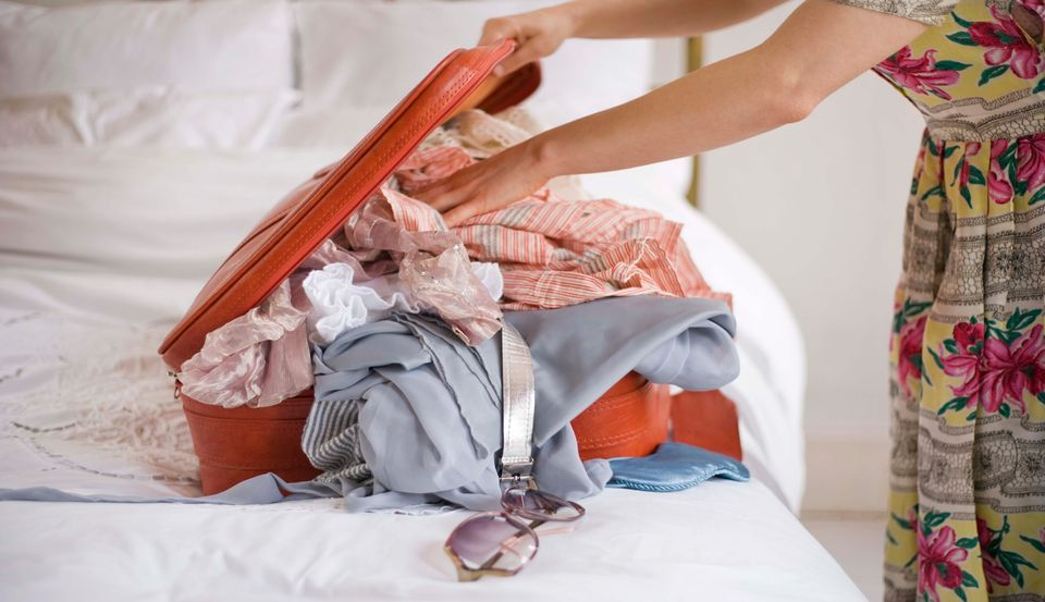 Woman packing overfilled suitcase - follow Skyscanner's packing tips for the best way to pack your suitcase