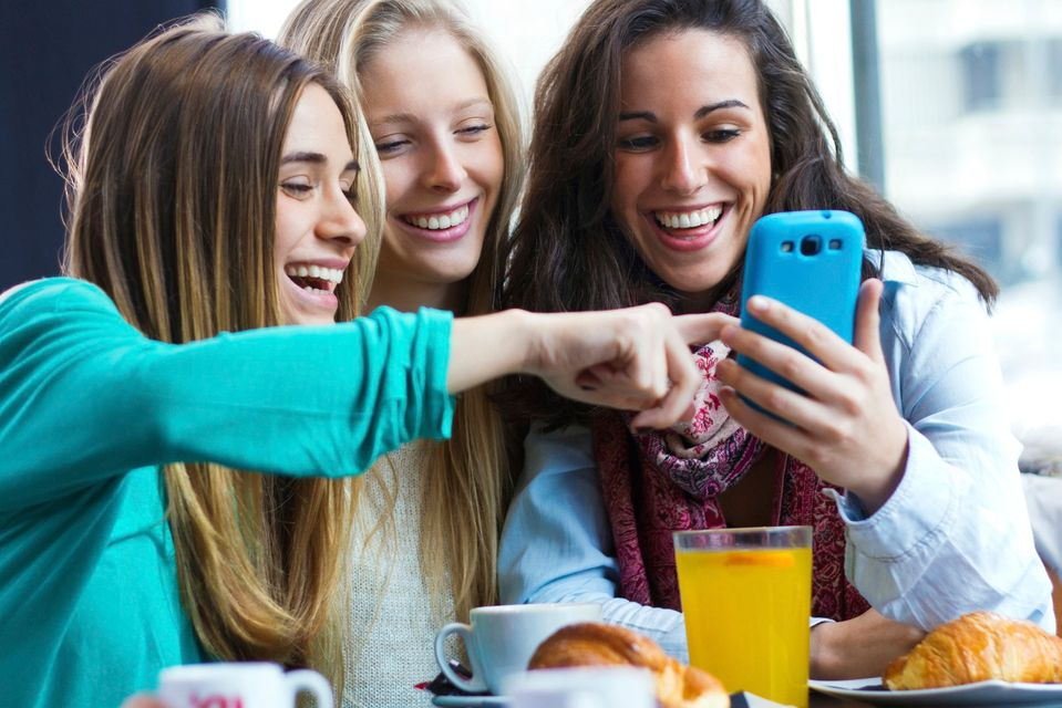group of 3 women looking at a smartphone