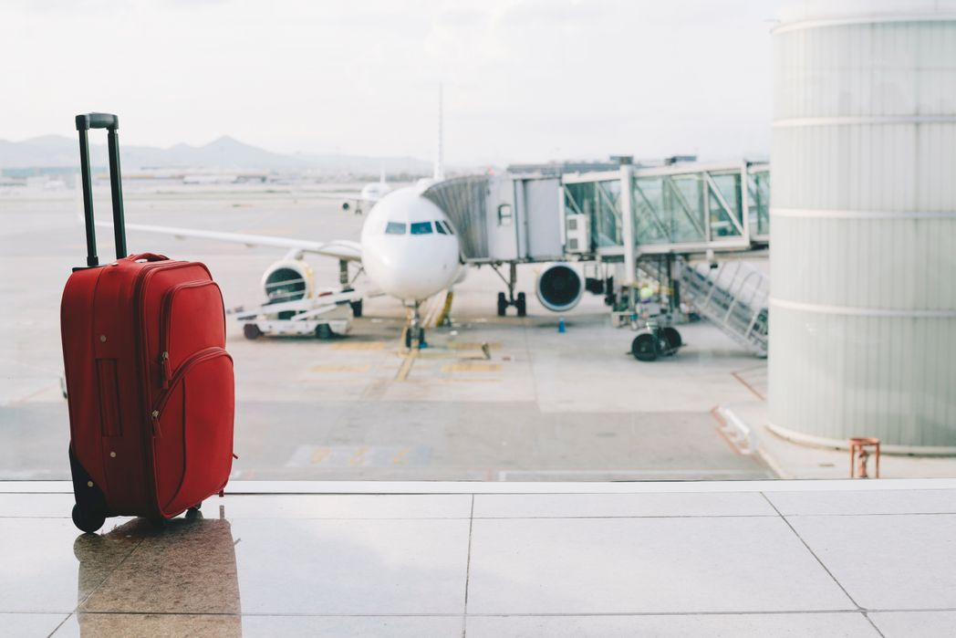 Red suitcase at airport, airplane in background