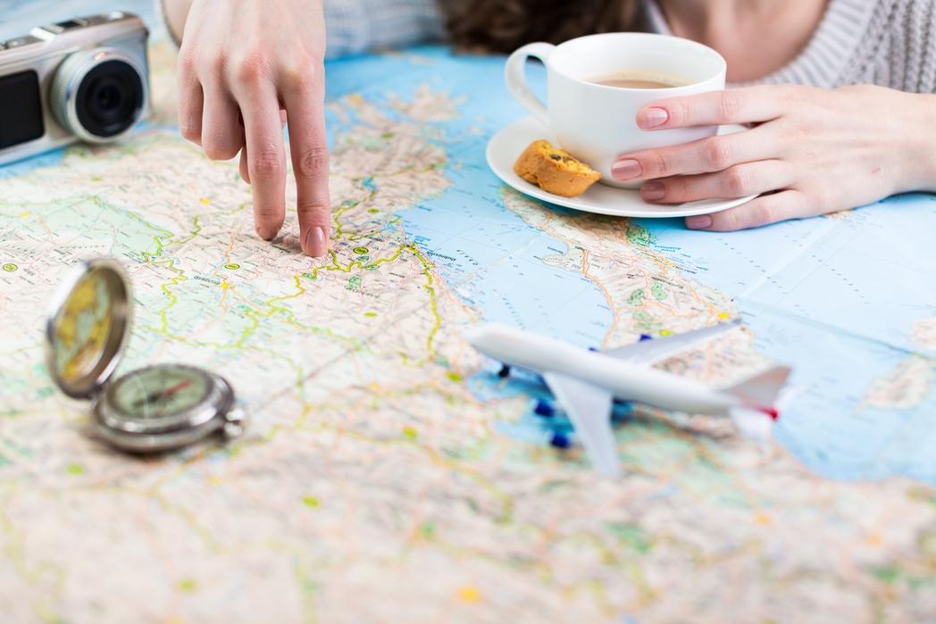 Γυναίκα κοιτάζει έναν χάρτη πίνοντας καφέ.