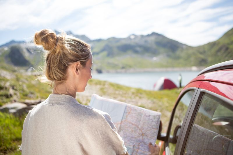 A woman holding a map while outside of her car. Camping tent next to a lake in the background.
