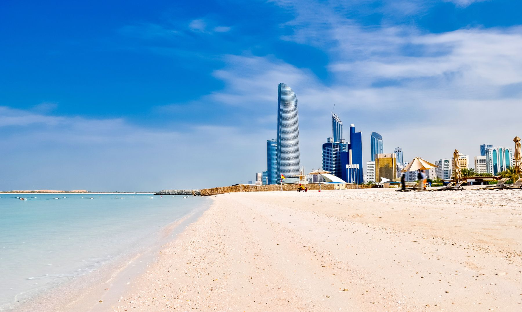 The skyscrapers of Abu Dhabi, as seen from a pristine white sand beach lapped by turquoise water.