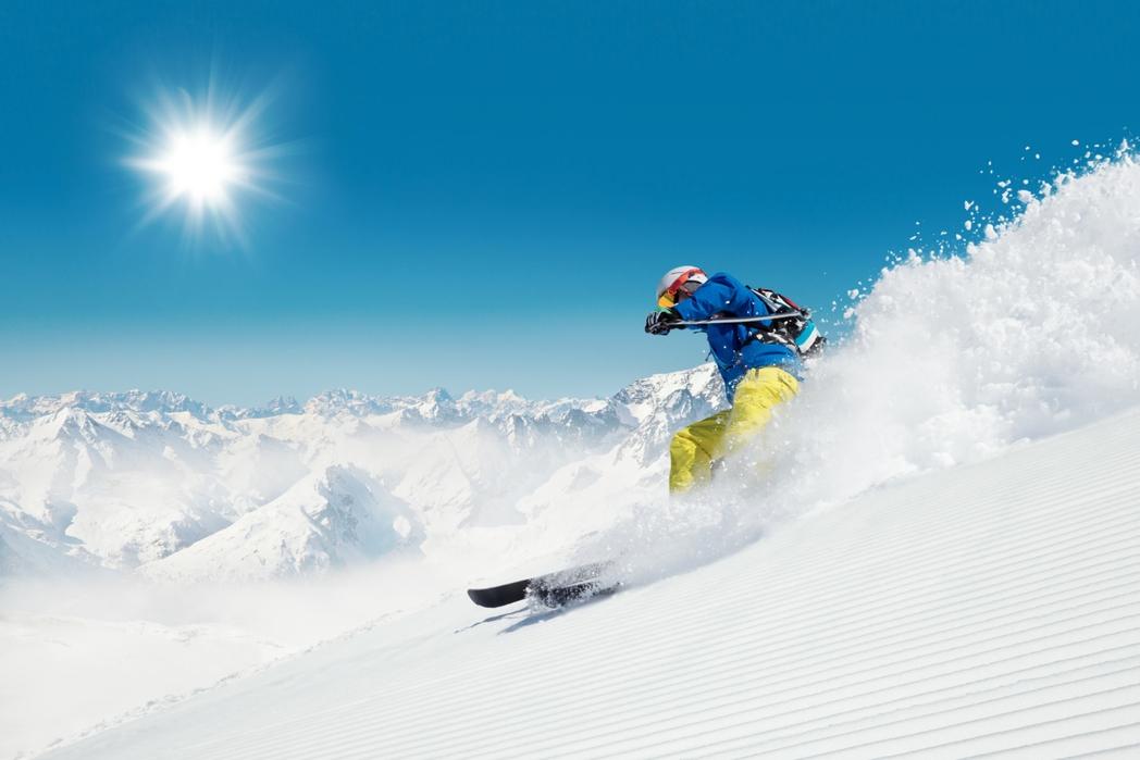 Σκιέρ διασχίζει το βουνό με ταχύτητα.