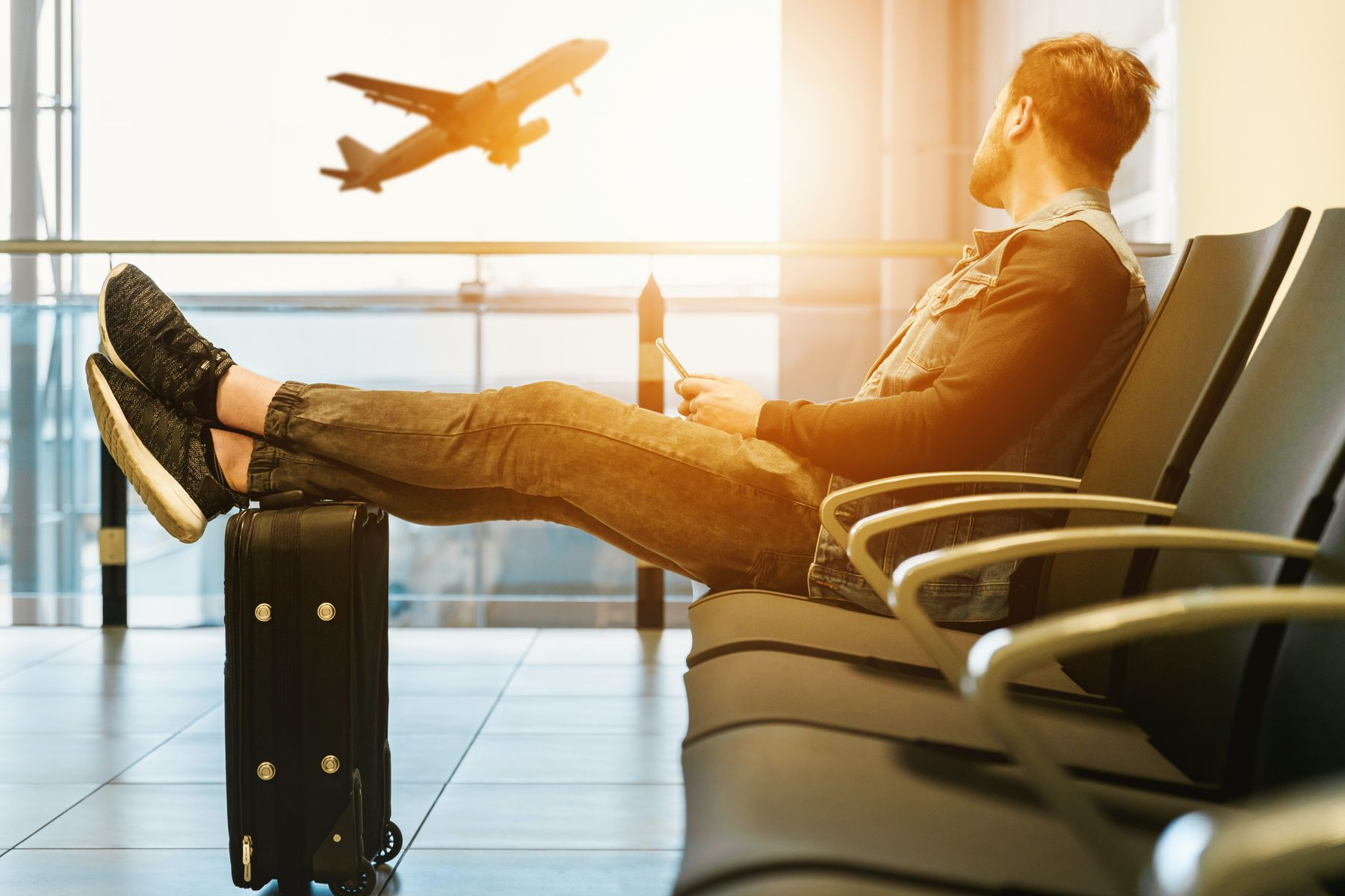 A man sits with his feet on his suitcase while a plane takes off in the background.